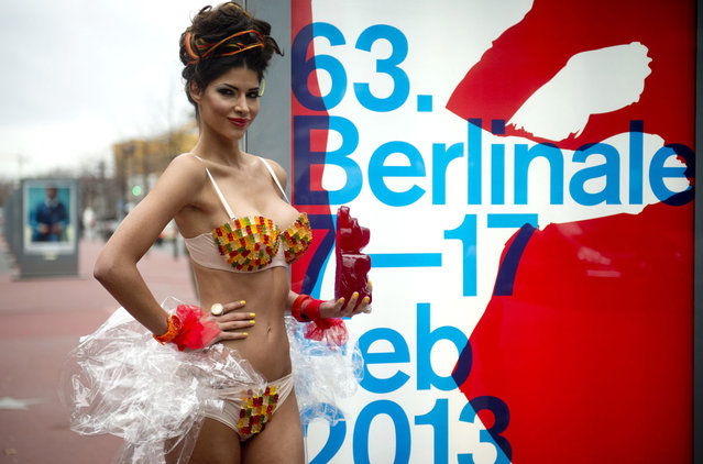 """German model Micaela Schaefer wearing a gummy bear bikini poses with a giant gummy bear on the """"Boulevard of the Stars"""" next to a Berlinale poster in Berlin on February 1, 2013. (Photo by Odd Andersen/AFP Photo)"""