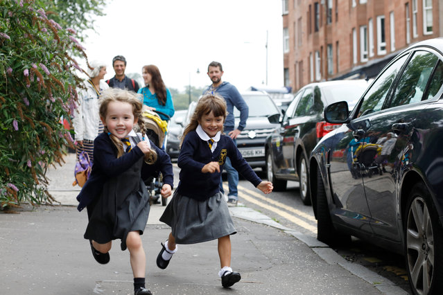 Róisín Casey-MacFadden (left) and Frieda-Sue Anson-Bernard arrive for their first day at Battlefield primary school in Glasgow, UK on August 11, 2020, as Scottish schools reopen after the coronavirus lockdown. (Photo by Katherine Anne Rose/The Observer)