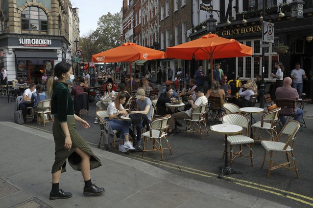 People sit outside on a street closed to traffic to try to reduce the spread of coronavirus so bars, cafes and restaurants can continue to stay open, in the Soho area of central London, Saturday, September 19, 2020. Fresh nationwide lockdown restrictions in England appear to be on the cards soon as the British government targeted more areas Friday in an attempt to suppress a sharp spike in new coronavirus infections. (Photo by Matt Dunham/AP Photo)