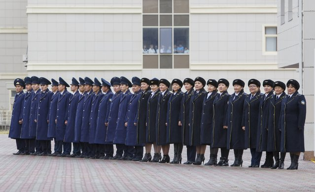 """Kazakhstan's railway staff line up to welcome foreign diplomats touring the International Centre of Boundary Cooperation """"Khorgos"""" at a border with China, in Kazakhstan, October 19, 2015. (Photo by Shamil Zhumatov/Reuters)"""