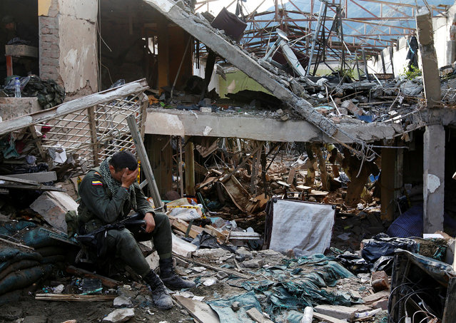 A police officer reacts amid the ruins of a police station which was destroyed by a bomb attack in the municipality of Inza in Cauca province December 7, 2013. (Photo by Jaime Saldarriaga/Reuters)