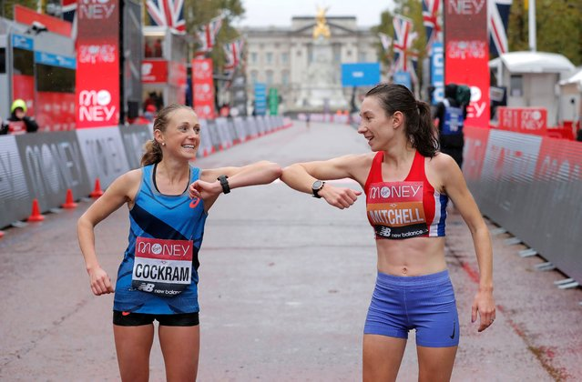 Natasha Cockram of Britain (L) and Naomi Mitchell of Britain (R) bump elbows after crossing the finish line in elite women's race during the London Marathon in London, Britain, 04 October 2020. (Photo by Tom Jenkins/The Guardian)