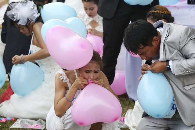 """Couples inflate balloons during one of the stages of the """"Running of the Brides"""" race in a park in Bangkok November 29, 2014. (Photo by Damir Sagolj/Reuters)"""