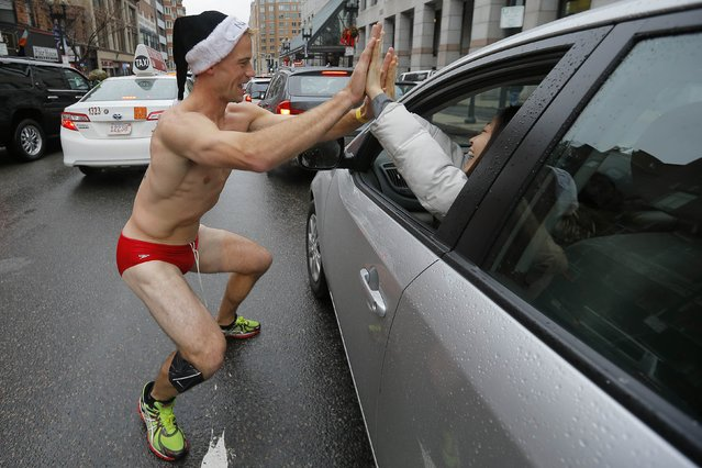 A runner (L) high fives a driver passing by after completing the 15th annual Santa Speedo Run, a charity run through the streets of the Back Bay, in Boston, Massachusetts December 6, 2014. (Photo by Brian Snyder/Reuters)