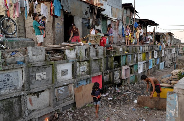 Makeshift houses are seen on top of apartment style tombs inside the municipal cemetery in Navotas city, north of Manila October 29, 2015. (Photo by Ezra Acayan/Reuters)