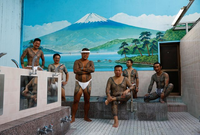 "Tattoo artist Asakusa Horikazu poses for a photograph with people who received tattoos from Horikazu and his father, at a Japanese public bath called a ""sento"" in Tokyo, Japan, September 24, 2020. ""It's been a problem at places like super sento and spas. I think it's because there's a strong image that they're against society. I take steps to make sure nothing that shouldn't be shown isn't, and I go into pools and things"" "" said Horikazu. (Photo by Kim Kyung-Hoon/Reuters)"