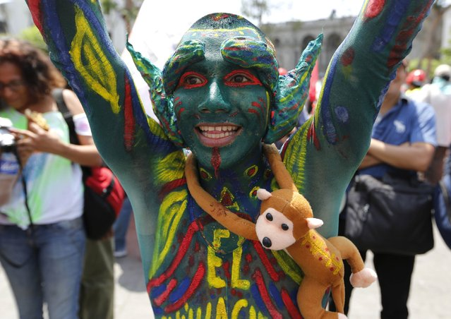 """An environmental activist marches at the """"People's Climate March"""" in downtown Lima, December 10, 2014. Thousands marched through Lima on Wednesday to protest against climate change as the United Nations climate summit, COP20, nears its final days. (Photo by Mariana Bazo/Reuters)"""