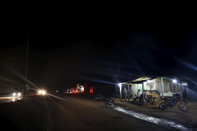 Residents talk in a restaurant at night in the village of Rio Pardo next to Bom Futuro National Forest, in the district of Porto Velho, Rondonia State, Brazil, August 31, 2015. (Photo by Nacho Doce/Reuters)