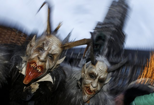 """Men dressed as """"Krampus"""" creatures take part in a parade at Munich's Christmas market, December 14, 2014. (Photo by Michaela Rehle/Reuters)"""