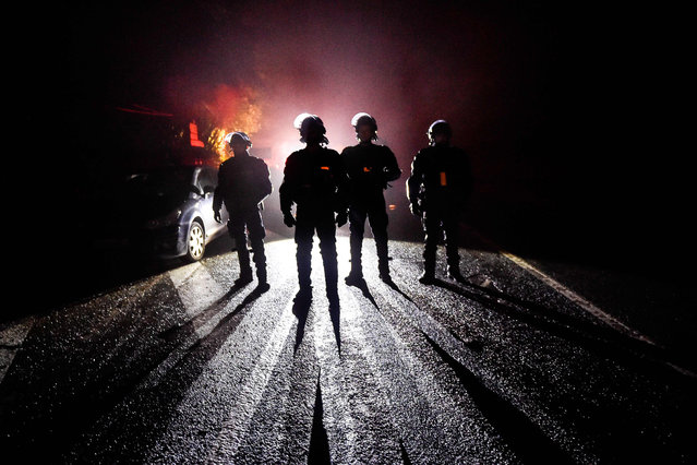 French riot police officers stand guard during the eviction of environmental protesters from the site, known as ZAD (Zone a Defendre – Zone to defend) of what had been a proposed new airport in Notre dame des Landes on April 9, 2018. (Photo by  Loic Venance/AFP Photo)