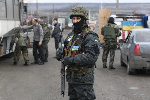 Ukrainian serviceman guards as his comrades check a civilian transport near the eastern Ukrainian town of Debaltseve in Donetsk region, December 24, 2014. (Photo by Valentyn Ogirenko/Reuters)