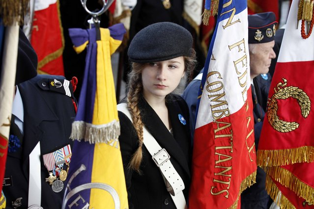 Charlotte, the niece of a French Veteran holds a France's Veterans flag at the tomb of the unknown soldier during the Armistice Day ceremony at the Arc de Triomphe in Paris, France, November 11, 2015. (Photo by Francois Mori/Reuters)