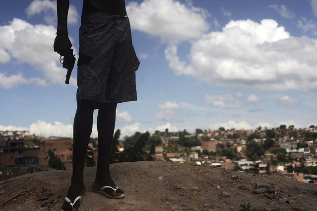 A Brazilian drug gang member nicknamed Giant, 17, poses with a gun atop a hill overlooking a slum in Salvador, Bahia State, April 11, 2013. One of Brazil's main tourist destinations and a 2014 World Cup host city, Salvador suffers from an unprecedented wave of violence with an increase of over 250% in the murder rate, according to the Brazilian Center for Latin American Studies (CEBELA). (Photo by Lunae Parracho/Reuters)