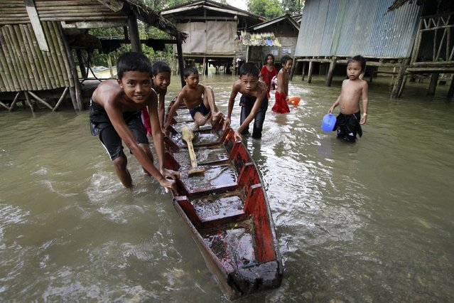 Children push a small boat through a flooded area in Yala province December 26, 2014. Many parts of the southern province remain flooded after recent heavy rains, local media reported. (Photo by Surapan Boonthanom/Reuters)