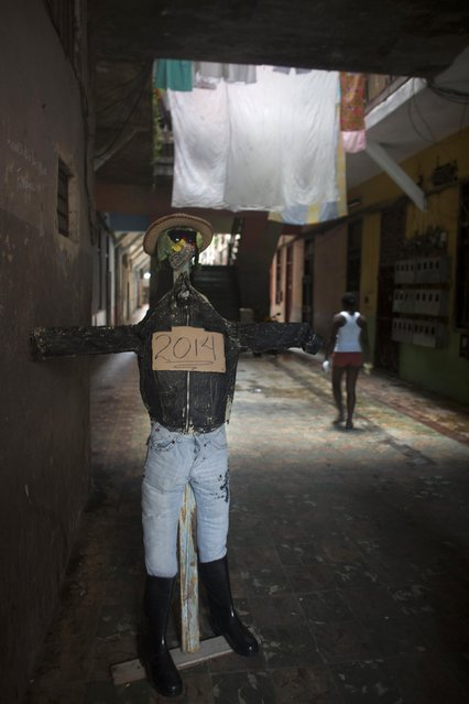 An effigy symbolising the year 2014 is seen at the entrance of a residential building in downtown Havana, December 29, 2014. The effigy will be burnt on midnight on December 31 as a way of welcoming the new year. (Photo by Alexandre Meneghini/Reuters)