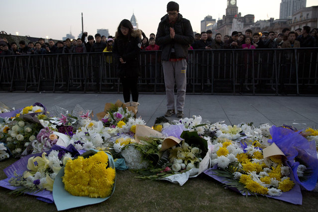 A man and a woman pray after laying flowers at the site of a deadly stampede in Shanghai, China, Thursday, January 1, 2015.  (Photo by Ng Han Guan/AP Photo)
