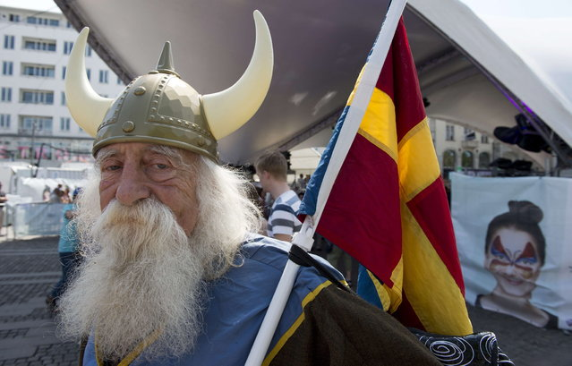 "A Malmo resident dressed in a viking costume holds a  composite ""scandinavian"" flag at a Eurovision public viewing area in downtown Malmo ahead of the finals of the 2013 Eurovision Song Contest on May 18, 2013. (Photo by John MacDougall/AFP Photo)"