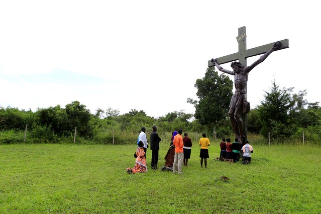 Catholic faithful pray in front of a cross of Jesus Christ erected by a roadside in Kakoge, north of Uganda's capital Kampala, October 18, 2015. Pope Francis makes his first pontifical visit later this month to Africa, where Catholicism has grown rapidly over the last few decades but now faces serious competition from Evangelical and Pentecostal churches, as well as Islam. The pontiff's trip to Africa, where an estimated 1 in 5 people is Catholic, takes in Kenya, Uganda and Central African Republic. (Photo by James Akena/Reuters)
