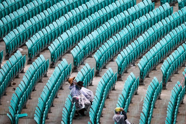 Spectators wearing face masks and rain covers sit in the stands as rain falls during day one of the third cricket Test match at the Sydney Cricket Ground (SCG) between Australia and India on January 7, 2021. (Photo by David Gray/AFP Photo)