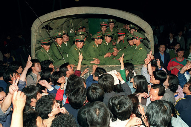 Pro-democracy demonstrators raise their fists and flash the victory sign in Beijing while stopping a military truck filled with soldiers on its way to Tiananmen Square on the day when then Prime Minister Li Peng declared Martial Law, May 20, 1989. (Photo by Catherine Henriette/AFP Photo)