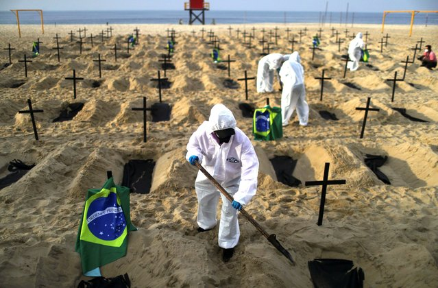 Activists of the NGO Rio de Paz in protective gear dig graves on Copacabana beach to symbolise the dead from the coronavirus disease (COVID-19) during a demonstration in Rio de Janeiro, Brazil, June 11, 2020. (Photo by Pilar Olivares/Reuters)