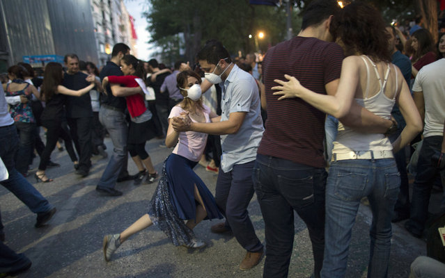 Protestors dance the tango at Gezi Park in Taksim Square on June 6, 2013 in Istanbul, Turkey. The protests began initially over the fate of Taksim Gezi Park, one of the last significant green spaces in the center of the city. The heavy-handed response of the police, Prime Minister Recep Tayyip Erdogan and his government's increasingly authoritarian agenda has broadened the rage of the clashes. (Photo by Uriel Sinai/Getty Images)