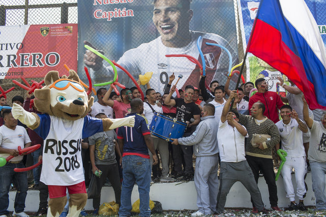 With a photo of Peruvian soccer star Paolo Guerrero in the background, inmates sing songs encouraging their soccer team in the San Juan de Lurigancho prison, in Lima, Peru, Thursday, May 24, 2018. (Photoby Rodrigo Abd/AP Photo)