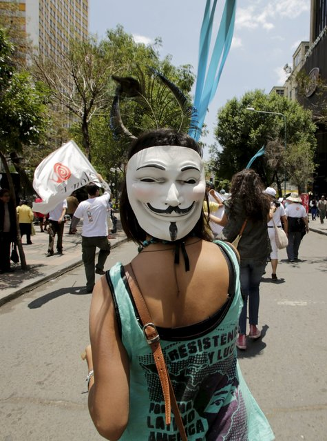 An activist wearing a Guy Fawkes mask participates in a rally held a day before the start of the Paris Climate Change Conference (COP21), in La Paz, Bolivia, November 29, 2015. (Photo by David Mercado/Reuters)