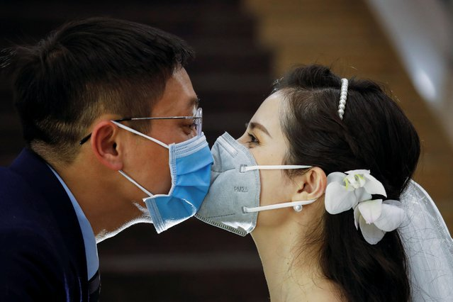 Vietnamese dentist Tran Phuong Thao and her husband Tran Minh Hieu wearing protective masks, kiss at their wedding ceremony during the coronavirus disease (COVID-19) outbreak in Hanoi, Vietnam on January 28, 2021. (Photo by Kham via Reuters)