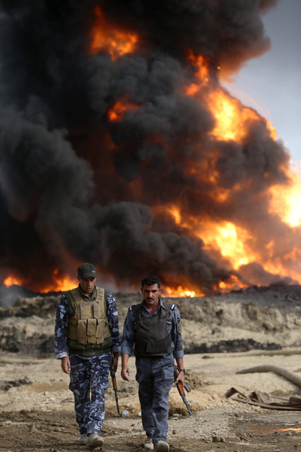 Iraqi security forces walk as fire and smoke rises from oil wells, set ablaze by Islamic State militants before fleeing the oil-producing region of Qayyara, Iraq, November 4, 2016. (Photo by Alaa Al-Marjani/Reuters)