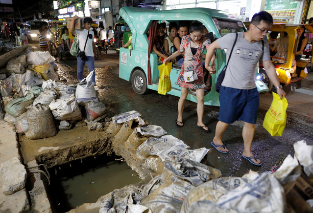 Tourists walk past a clogged sewer and uncollected sacks containing waste from the sewers along a road at Boracay in Philippines on April 9, 2018. (Photo by Erik De Castro/Reuters)