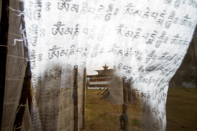 """""""Temple Of The Divine Madman Through Prayer Flags"""". Chimi Lhakhang, or more commonly known as the Temple Of The Divine Madman, is located in the hills of the Punakha District in Bhutan. The day was gray and windy on my visit to the temple, which I had already shot once before. Trying something new, I used a wide-angle lens and the built-in flash on my Canon 7D to create a shadow on the prayer flags through which to shoot. It took a few tries as the wind whipped the flags in front of my lens. The Sanskrit mantra Om Mani Padme Hum is written over and over on the flags. (Photo and caption by Peter Carey/National Geographic Traveler Photo Contest)"""