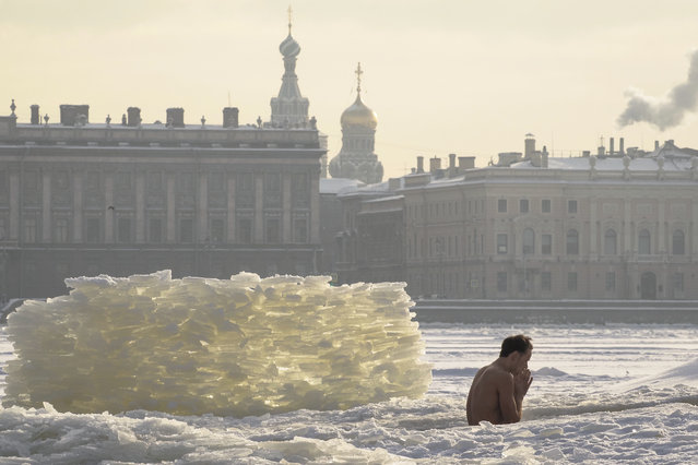 A man bathes in an ice hole in the Neva River St. Petersburg, Russia, Wednesday, February 10, 2021. The temperature in St. Petersburg is –15C ( 5 °F). (Photo by Dmitri Lovetsky/AP Photo)