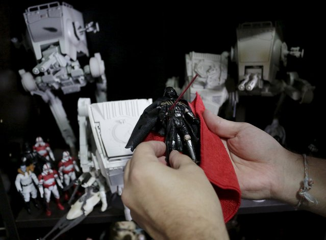 Mexican collector Pablo Perez, holds up a Star Wars Dark Vader toy next to his toy collection of Star Wars characters and items at his home in Monterrey, Mexico December 12, 2015. (Photo by Daniel Becerril/Reuters)