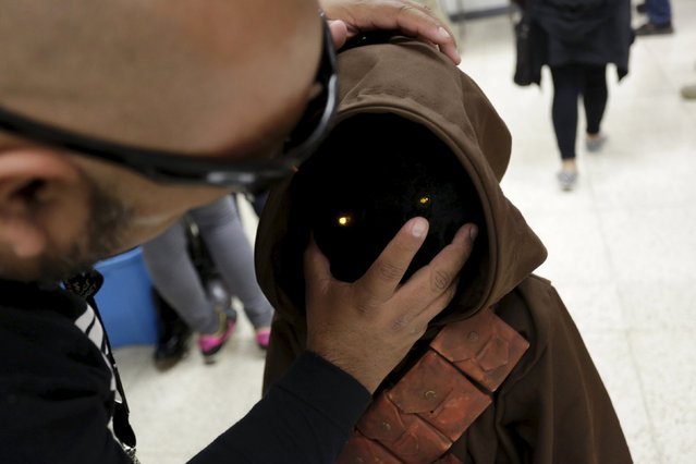A man helps a child to dress as Jawa, a character from the Star Wars movie series, during an event organised by Star Wars fan club Monterrey in Monterrey, Mexico, December 13, 2015. (Photo by Daniel Becerril/Reuters)