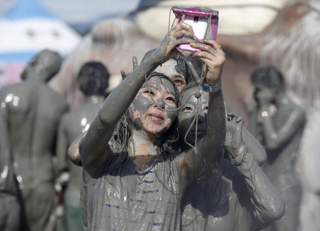 Tourists take pictures with a mobile phone after playing in the mud during the Boryeong Mud Festival at Daecheon beach in Boryeong, about 190 km (118 miles) southwest of Seoul, July 19, 2013. About 2 to 3 million domestic and international tourists visit the beach during the annual mud festival, according to the festival organisers. (Photo by Lee Jae-Won/Reuters)