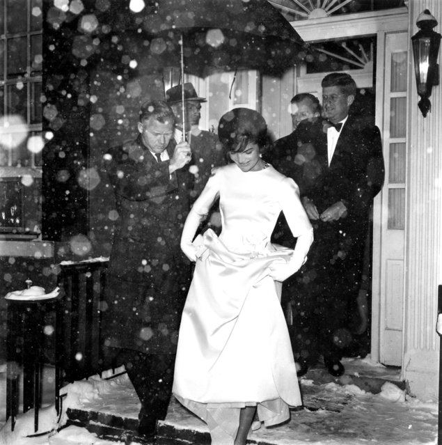Jacqueline Kennedy lifts the skirt of her inaugural ball gown as she and her husband, President-elect John F. Kennedy, leave their Georgetown home in the snowfall en route to the inaugural concert in Washington, D.C., January 19, 1961. (Photo by AP Photo)