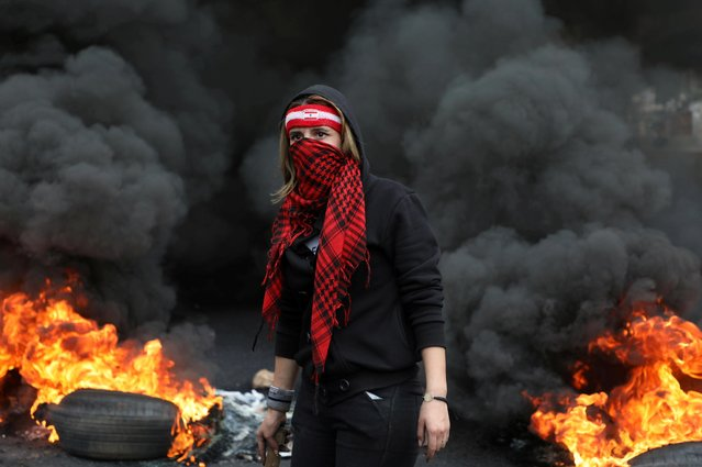 A demonstrator stands near a burning fire blocking a road, during a protest against the fall in Lebanese pound currency and mounting economic hardships, in Zouk, Lebanon on March 8, 2021. (Photo by Mohamed Azakir/Reuters)