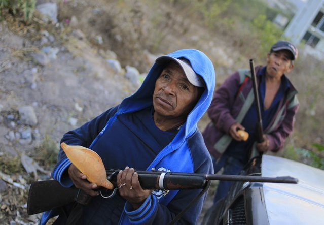 Members of the Community Police from the FUSDEG (United Front for the Security and Development of the State of Guerrero) hold bread as they stand guard in the early morning at an entry to Petaquillas, on the outskirts of Chilpancingo,  in the Mexican state of Guerrero, January 31, 2015. (Photo by Jorge Dan Lopez/Reuters)