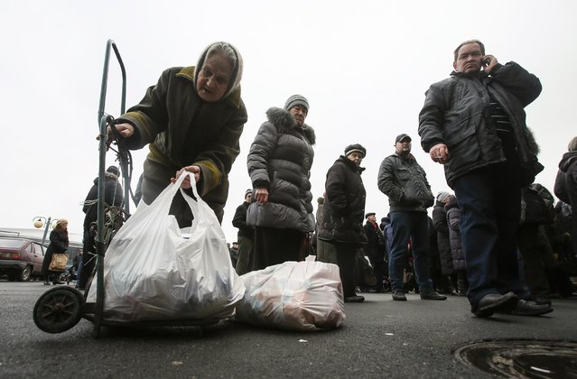 A woman picks up a bag with humanitarian aid in front of a delivery point in Donetsk February 3, 2015. (Photo by Maxim Shemetov/Reuters)