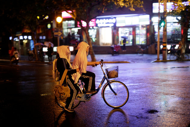 Girls ride a bike on a street during a rainy day in Shanghai, China November 7, 2016. (Photo by Aly Song/Reuters)