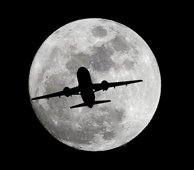 An airplane crosses a nearly full-moon on its way to Los Angeles International Airport near Whittier, Calif., Thursday, December 24, 2015. Not since 1977 has a full moon dawned in the skies on Christmas. (Photo by Nick Ut/AP Photo)