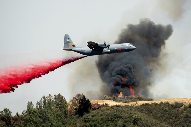 An air tanker drops retardant on the River Fire burning near Lakeport, Calif., on Tuesday, July 31, 2018. (Photo by Noah Berger/AP Photo)