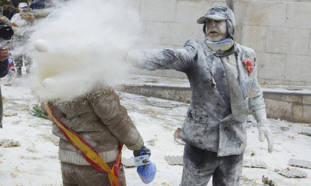 "A reveller throws eggs and flour to another participant as they take part in the ""Enfarinats"" battle in the southeastern Spanish town of Ibi on December 28, 2015. (Photo by Jaime Reina/AFP Photo)"