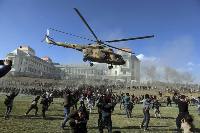 A military helicopter flies over people during the Afghan Security Forces Exhibition, at the Darul Aman Palace in Kabul, Afghanistan, Wednesday, March 3, 2021. The three-day military exhibition in Kabul allowed civilians to have a first hand view and take pictures of weaponry used by Afghan Security forces. (Photo by Rahmat Gul/AP Photo)