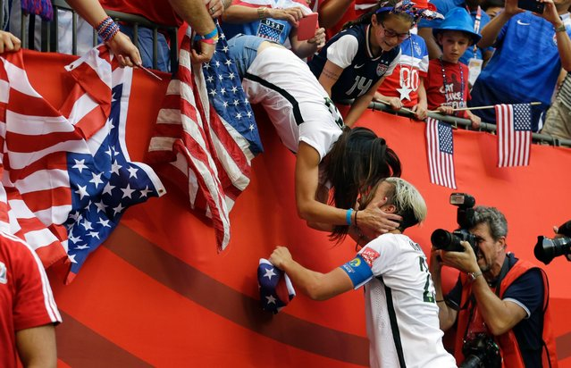 United States' Abby Wambach, right, gets a kiss from her wife, Sarah Huffman, after the U.S. beat Japan 5-2 in the FIFA Women's World Cup soccer championship in Vancouver, British Columbia, Canada, July 5, 2015. (Photo by Elaine Thompson/AP Photo)