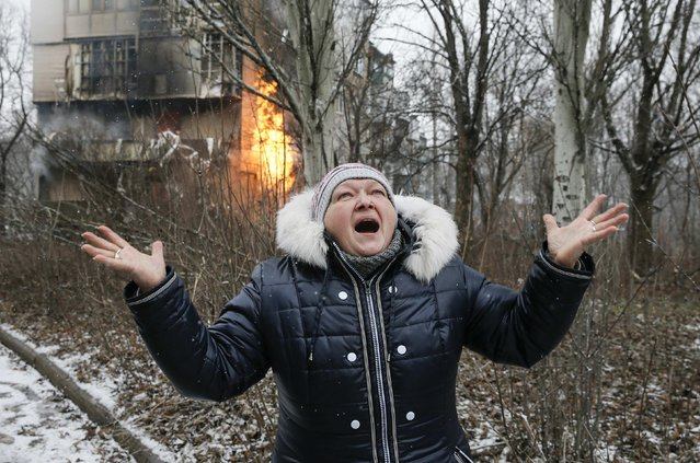 A woman reacts as the residential block (back) in which she lives in burns, a result of recent shelling according to locals, on the outskirts of Donetsk, eastern Ukraine February 9, 2015. (Photo by Maxim Shemetov/Reuters)