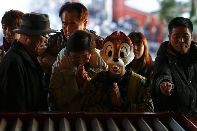 A boy wears a comic character hat as he prays at the Sensoji temple ahead of the New Year holidays in Tokyo, Japan December 30, 2015. (Photo by Thomas Peter/Reuters)