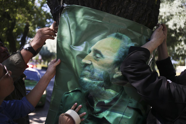 Supporters of Fidel Castro hang his photo outside Cuba's embassy in Santiago, Chile, Saturday, November 26, 2016. Castro, who led a rebel army to improbable victory, embraced Soviet-style communism and defied the power of 10 U.S. presidents during his half century rule of Cuba, died at age 90 late Friday, Nov. 25. (Photo by Esteban Felix/AP Photo)