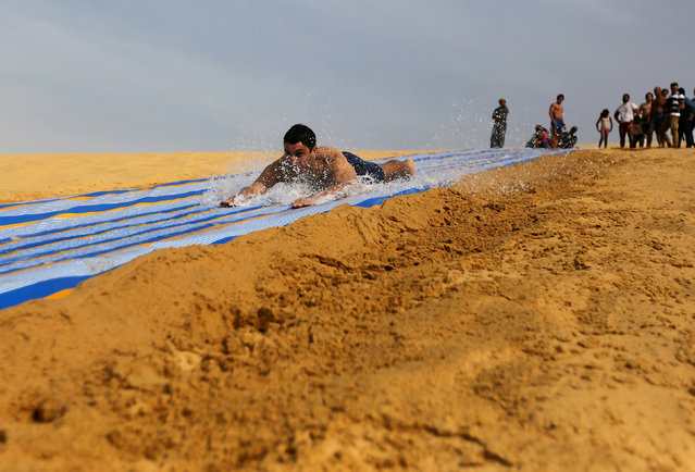 A man slides down a ramp into the lake in Wadi el-Rayan Fayoum, Egypt, November 18, 2016. (Photo by Mohamed Abd El Ghany/Reuters)